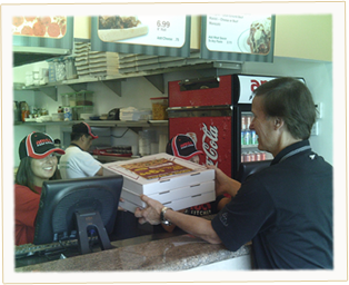 Our Ameci Team Member serving another happy customer hs pizzas.